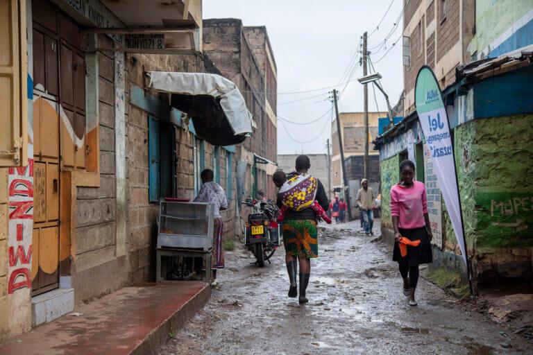 People walk down a narrow, rainy street.